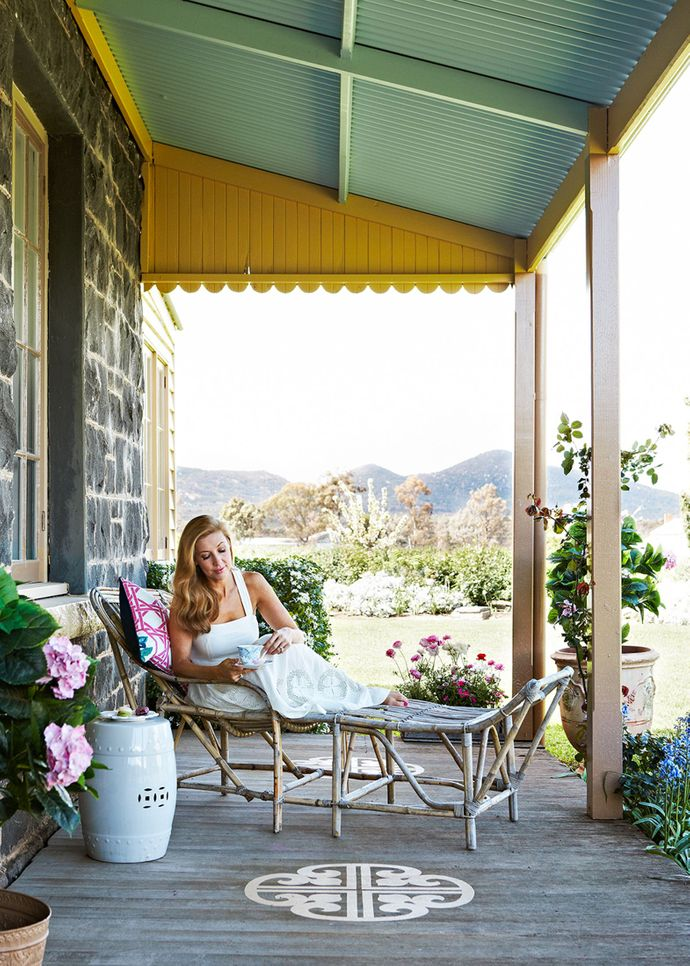 """Catriona relishes the fresh air and stunning surrounds from her rattan daybed, a wedding gift from a friend, landscape designer Paul Bangay. """"Just quietly, I also love the fact that in the country you can't see any neighbours,"""" she says with a smile. The painted floor decal was inspired by a trip to South America, and makes a striking statement."""