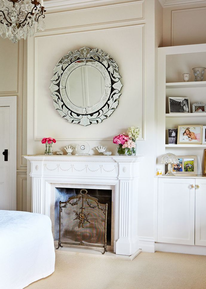 """A beautifully restored fireplace takes pride of place in Catriona and James's bedroom. The mantelpiece houses favourite treasures such as cherished Lalique glassware, with freshly picked roses adding a flourish of pink. """"Roses are the superheroes of our garden, having toughed out the drought,"""" Catriona says. """"They're so hardy, yet utterly beautiful."""""""