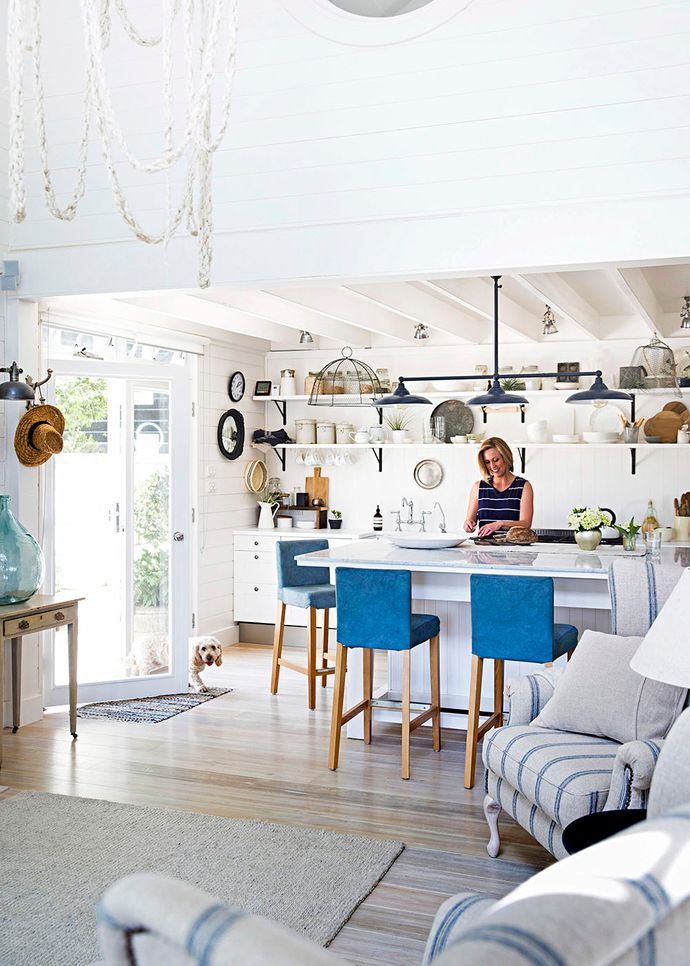 """A must-have in the bright kitchen is a double-sized marble island bench, made by Martyn, which has storage underneath and is the inside dining spot for the family. """"We can actually fit 10 around it,"""" says Tara. Open shelves that house dinnerware were originally a temporary inclusion. """"A couple of Christmases ago, I said, 'I need some shelves!' and Martyn chucked them up for me,"""" says Tara with a laugh – but they have since grown on the couple and look set to become permanent. """"It's kind of good when people come over because they know where everything is and they can just help themselves,"""" adds Tara. A Belgian-style trio of lights, from Town And Country Style, lends a slight industrial edge, while custom-covered Ikea stools provide a tinge of blue."""
