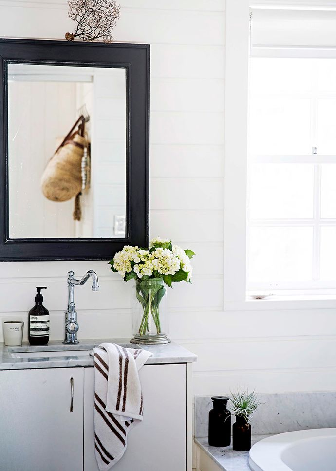 A marble-topped vanity and bath surround connect the bathroom stylistically to the kitchen.