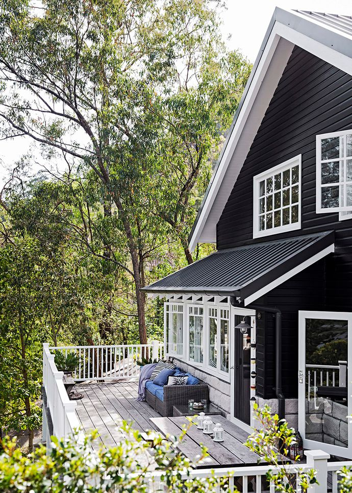 """With its gable roof and all-wood exterior, TV host Tara Dennis's family home sits beautifully with its rugged natural surrounds. """"I'm hoping that it will age over time and just sit into the hill,"""" says Tara of the cottage her husband Martyn spent a year building. The inky exterior swathed in British Paints Black Ace supplies a Hamptons vibe but also looks very at ease in the Australian bush."""