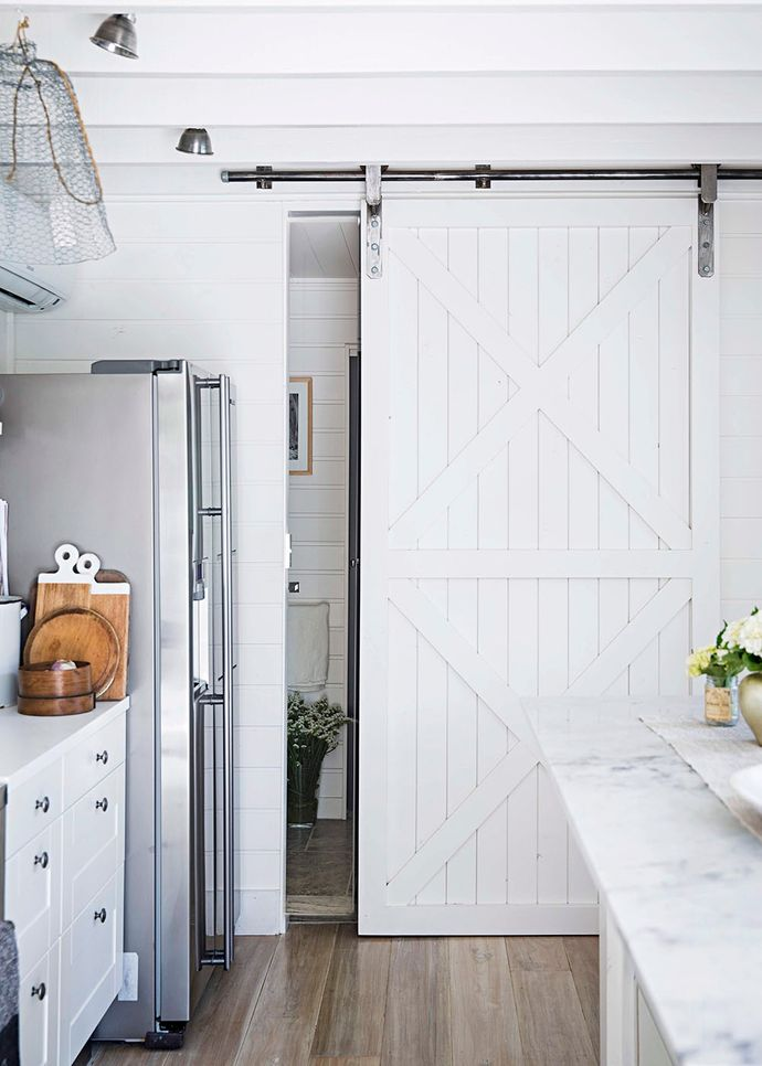 A custom-built barn door, made (again!) by the clever Martyn, this time from floorboards, separates the laundry and chic family bathroom from the living space. Wide blackbutt boards, painted in Porter's Paints Original Lime Wash, were a beautiful choice for the floors.